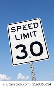 Thirty miles per hour speed limit sign against a partly cloudy sky.
