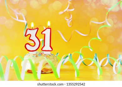 Thirty one years birthday. Cupcake with burning candles in the form of number 31. Bright yellow background with copy space