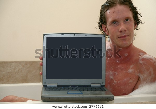 Thirty something man in bubble bath with laptop.  Screen facing camera.