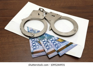 Thirty thousand tenge are prepared for a bribe. The handcuffs lie on an envelope from which Kazakh money is seen. The concept of corruption and violation of law in Kazakhstan.