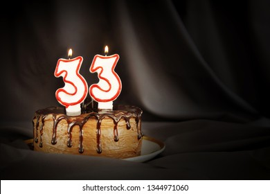 Thirty three years anniversary. Birthday chocolate cake with white burning candles in the form of number Thirty three. Dark background with black cloth