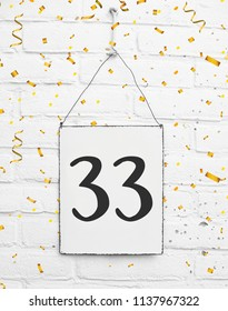thirty three years old birthday congratulations text with golden confetti sign white brick background
