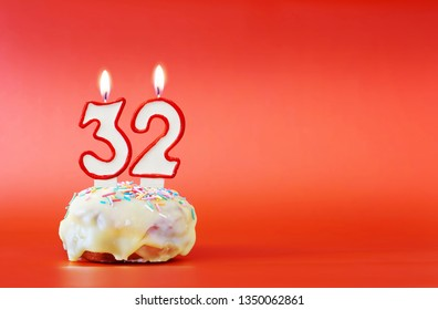 Thirty two years birthday. Cupcake with white burning candle in the form of number 32. Vivid red background with copy space