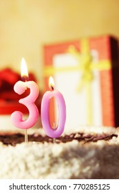 Thirty years. Birthday cake with burning candles and gifts