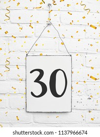 Thirty years old birthday congratulations text with golden confetti sign white brick background number 30