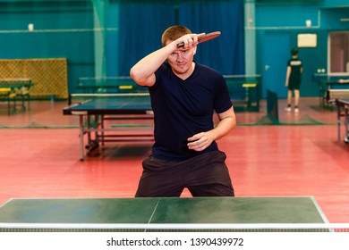 thirty-year-old man in black sports uniform playing table tennis in the gym. roll right in table tennis indoors