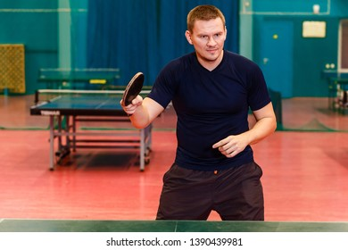 thirty-year-old man in black sports uniform playing table tennis in the gym. Ping pong