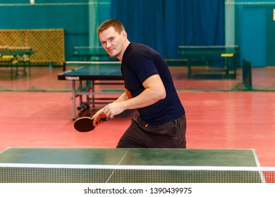 thirty-year-old man holding a racket for table tennis indoors
