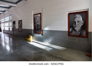 THIRUVANNAMALAI, TAMILNADU, INDIA, SEPTEMBER 21, 2015: Prayer hall of Ramanashramam, the home of Ramana maharshi, Advaita Vedanta philosopher. A woman meditates in the morning among pictures of rishi.