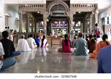 THIRUVANNAMALAI, TAMILNADU, INDIA, SEPTEMBER 21, 2015: Ramanasramam. Visitors and devotees sitting on the floor attend pooja and mantra chanting in the morning. The shrine is seen in the background.