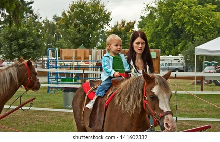 This 1 year old toddler girl is riding a first pony ride with her mom walking beside her.  Rural lifestyle family image.