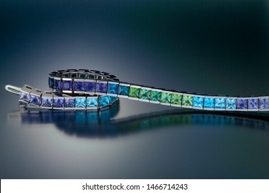 This 14K white gold link tennis bracelet is channel set with a graduated range of cool colored gemstones including amethyst, peridot, aquamarine, blue topaz and iolite. Shown on a black background.