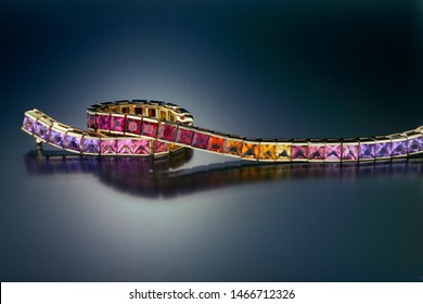 This 14K yellow gold link tennis bracelet is channel set with a graduated range of warm colored gemstones including amethyst, garnet, citrine and iolite. Shown on a black reflective background.