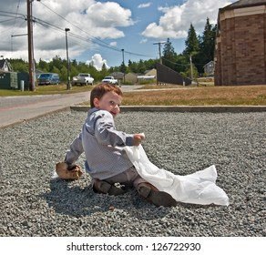 This 4 year old Caucasian boy is picking up garbage outside, a crumpled paper bag litter into a white trash bag.  He's helping the environment to stay green.