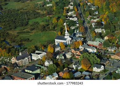 This is an aerial view of the New England village of Stowe. It is along scenic Route 100. There is autumn foliage in the trees. It is a typical looking small New England town.