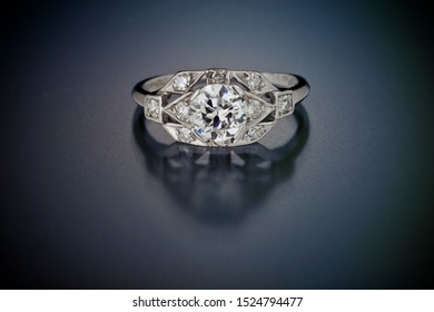 This antique diamond engagement ring with a one plus carat center stone is surrounded by accent side diamonds and set in platinum. Shown on a black reflective background.