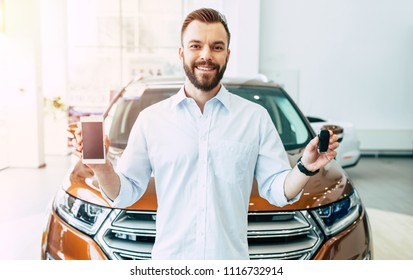 With this app on mobile much easier buying a car. Smiling handsome customer in dealership shows smart phone and car keys in camera