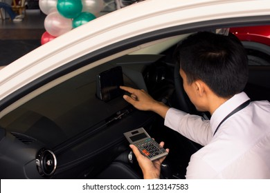 This asian man Calculating calculator in car career saleman for business finance on car showroom blurry background.for automotive automobile or transportation