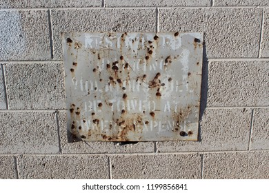 This battered and weathered sign continues to bake in the sun, and warn violators that parking is prohibited.  Abused and rusting, this barely legible sign is attached to a pale gray brick wall.