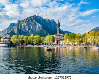 This is the Bay of the city of Lecco in spring where we can see some boats at anchor and where you see the road along the Lake with the walk and the tree-lined Avenue.