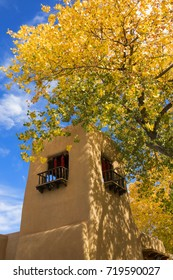 This beautiful autumn day, with bright yellow cottonwood leaves, rich blue sky and warm adobe architecture is the perfect fall photo of Santa Fe New Mexico.