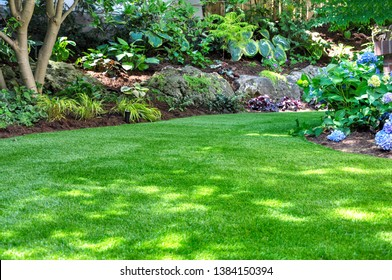 This beautiful backyard woodland garden features a maintenance free lawn made of realistic looking artificial grass, a huge landscaping trend for small spaces.