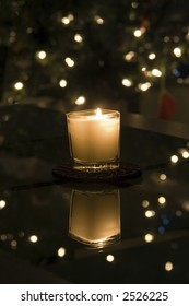 This beautiful candle is sitting on a family room table in-front of the christmas tree.