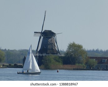 This beautiful historic windmill stands by a lake in Holland, on which a  sailing boat sails