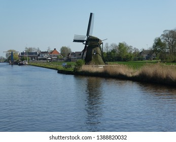 This beautiful historic windmill stands by a lake in Holland