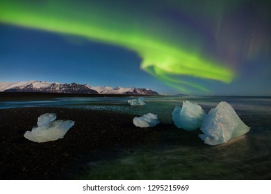 This beautiful northern lights or aurora borealis in Iceland dancing over the above Jokulsarlon glacier lagoon and black beach with icebergs. Beautiful Iceland in winter.Green aurora Kp 4 polar lights