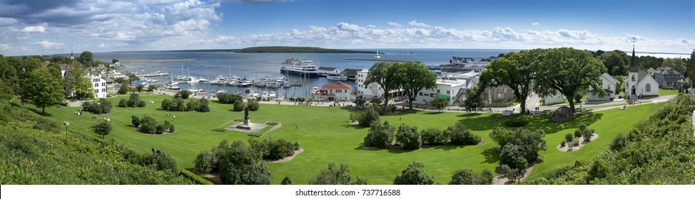 This beautiful panoramic scene of Mackinac Island Michigan and picturesque State Harbor Marina is shot from the hill along Fort Mackinac.
