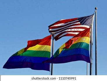 This is  beautiful picture of the U.S.  flag flying high. Along with two lgtbq rainbow flags.