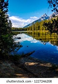 This is a beautiful view from the Leigh Lake Trail in Grand Teton National Park in Wyoming. Reflections of sky and clouds upon the calm lake are seen.