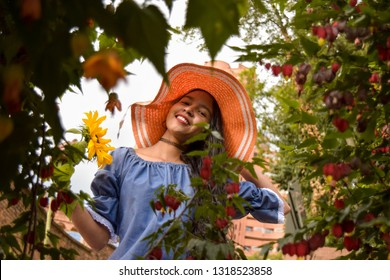 This beautiful woman is enjoying a sunny day with her magnificent sunflower in her hands. This girl wears a sun hat and a sexy blue dress. Around it there is a foliage of leaves and flowers.