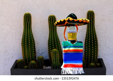This beer bottle is dressed in a sombrero and poncho getting ready to celebrate the Mexican holiday of Cinco de Mayo.  Also know as the 5th of May.
