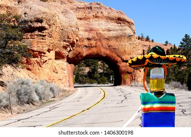 This beer bottle is wearing a poncho and a sombrero and is in front of a tunnel near Bryce Canyon, Utah.
