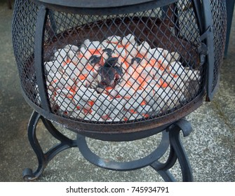 This is a black iron fire pit with red hot burning briquettes going.