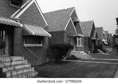 This is a black and white image of a row of single family houses. They are located on the south side of Chicago. They are brick houses with striped awnings over the front window and front door.