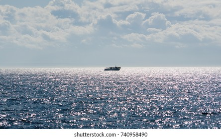 This is a boat sailing in a bright sunny day with dramatic cloudy skies and sparkling ocean.