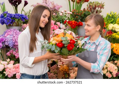 This bouquet is marvelous. Smiling florist and attractive female customer holding a beautiful floral arrangement