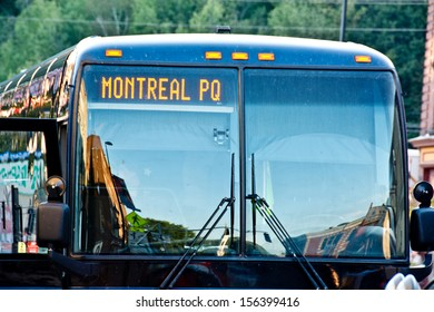 This bus is headed straight to Montreal. The stickers on the bus door prove that the bus has passed state inspections.