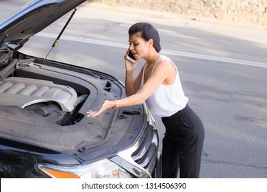 This car doesn't work! Side view of beautiful young woman looking at open vehicle hood and talking on mobile phone while standing near car outdoors