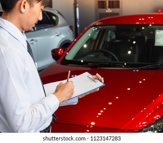 This career man saleman business inspection writing on notepad or book, paper with car blurry background.for transport automobile automotive image.