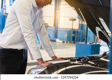 This career man saleman business inspection writing note on notepad or book, paper with car blurry background.for transport automobile automotive image