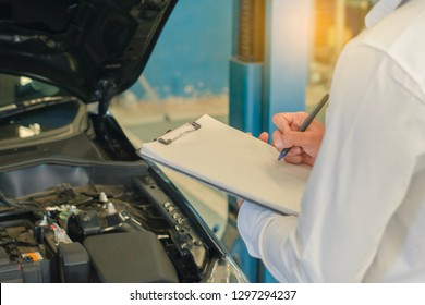This career man saleman business inspection writing note on notepad or book, paper with car blurry background.for transport automobile automotive image.