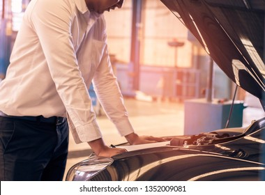 This career man saleman business inspection writing note on notepad or book, paper with car blurry background.for transport automobile automotive Illustrative editorial image