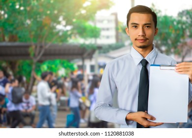 This career saleman or business man inspection writing on notepad or  book, paper with building and confused people in city blurry background.metaphor business success copy space for advertising image