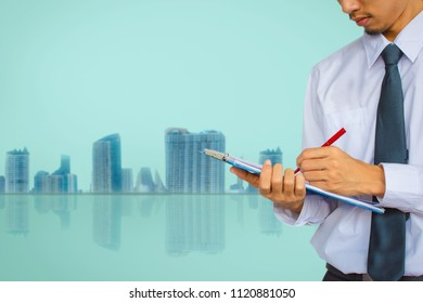 This career saleman or business man inspection writing on notepad or book, paper with building in city blurry background.metaphor business success copy space for advertising image