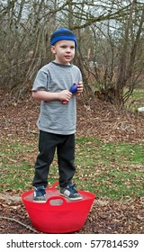 This Caucasian 5 year old boy is playing outside and standing on a red bucket that is frozen solid ice.  He's wearing a blue stocking cap, black sweat pants and holding a throwing toy.