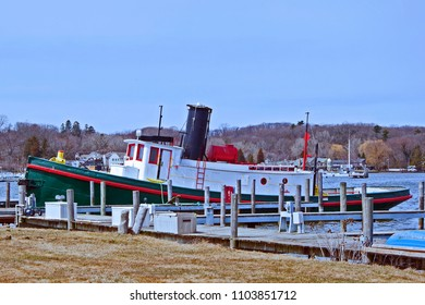 This charming green, red & white tug boat is tied to a white & grey wood dock & weathered wood pylons on the Kalamazoo River in Saugatuck Michigan during early spring awaiting the bustle of summer.
